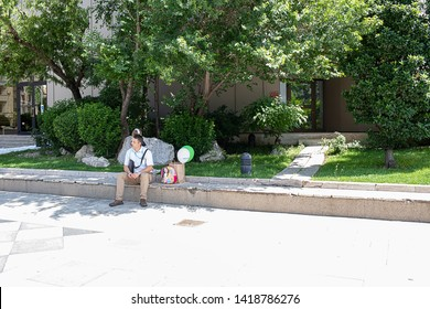 Bucharest, Romania - May 30, 2019: Dad with his daughter relaxing on a side of the street.