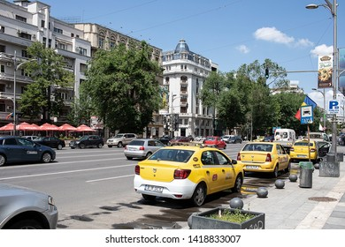 Bucharest, Romania - May 30, 2019: Yellow cabs in Nicolae Balcescu Boulevard near the University Square.