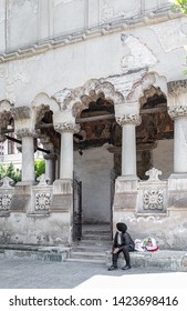 Bucharest, Romania - May 30, 2019: Poor woman sitting on the stairs in front of the Coltea church, one of the architectural monuments most representative of the Brâncoveanu style age.