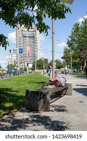 Bucharest, Romania - May 30, 2019: Antagonism between poverty and wealth downtown Bucharest - poor man sleeping on a bench in the street and luxury Intercontinental hotel in the background.