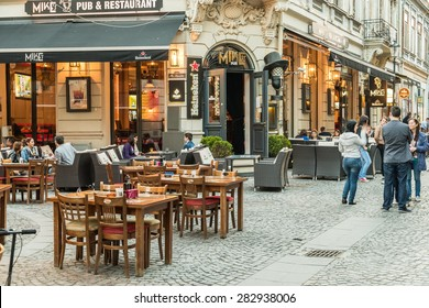 BUCHAREST, ROMANIA - MAY 31, 2015: Tourists Visiting And Having Lunch At Outdoor Restaurant Cafe Downtown Lipscani Street, one of the most busiest streets of central Bucharest.