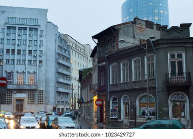 BUCHAREST, ROMANIA - OCT 10, 2106: Small street in a city center of Bucharest in the rain. Bucharest is the capital of Romania.