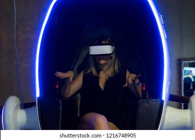 Bucharest, Romania, October 20, 2018: Attractive woman experiencing a virtual reality headset while sitting on a designated simulation shell chair that induces coordinated motion with the VR program.