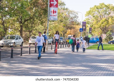 BUCHAREST, ROMANIA, - October 26, 2017: Woman using electric scooter on the street in a sunny day. Illustrative editorial content.