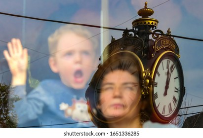 Bucharest, Romania - October 28, 2018: Mother and son looks out the window of an old Romanian V56 tram at a street iron work clock at a trams parade in downtown Bucharest. Image for editorial use only