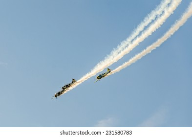 BUCHAREST, ROMANIA - OCTOBER 4, 2014. Aerobatic airplane pilots training in the sky of the city. Colored airplane with trace smoke.