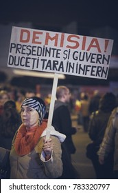 """Bucharest, Romania - October 6, 2013: Woman holds a sign reading """"Resignation! President and Government lead our country into the chaos"""" during the riot against cyanide gold mining in Rosia Montana."""