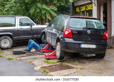 BUCHAREST, ROMANIA - SEPTEMBER 12, 2015: Man working under his Wolkswagen Polo car at a small car service trying to fix a steering system issue due to bad roads