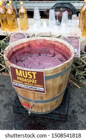"""Bucharest, Romania - September 14th 2019: Sweet drink made from grape juice named """"must"""" """"vin"""" """"vin rosu"""". Fresh cold pressed grape juice made during food festival. Sugary beverage natural sugar drink"""