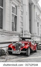 Bucharest, Romania - SEPTEMBER 2, 2015. Red Morgan MG vintage car in front of a white historic building in Bucharest Romania on September 2, 2015