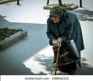 Bucharest/Romania - 05.01.2019: Hunched old poor woman with a walking stick. Old woman begging for food in Bucharest.