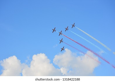 Bucharest,Romania - July 28th 2018:Formation of six stunt jets flying on a cloudy blue sky leaving red and white smoke trails