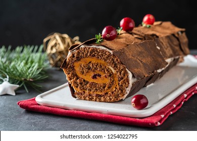 Buche de Noel. Traditional Christmas dessert, Christmas yule log cake with chocolate cream, cranberry. On stone gray background with Christmas tree branches.