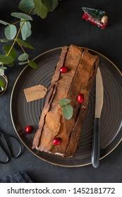 Buche de Noel. Traditional Christmas dessert, Christmas yule log cake with chocolate cream, cranberry. Copy space.