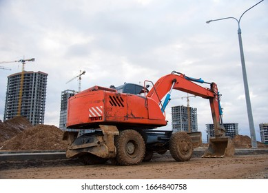 Bucked wheel excavator digs ground at a construction site for installing concrete storm pipes. Backhoe the digging pipeline ditch. Commercial and Public Civil Work Contracting, trenching, tamps soil