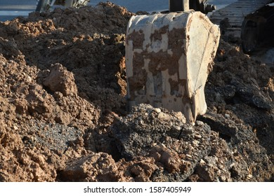 The bucket of the backhoe or tractor was digging out of the pit by the plumber's repairman.