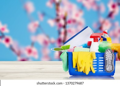 Bucket or basket with cleaning items on wooden table and blurry pink flowers tree background. Washing set with copy space banner.