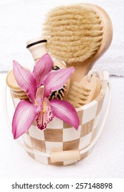 Bucket with brushes and orchid