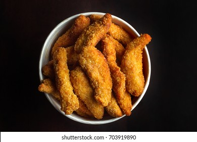 Bucket of chicken nagets. On a black background, top view.