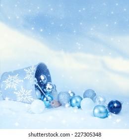 Bucket of Christmas balls on winter background.