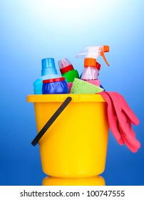 Bucket with cleaning items on blue background