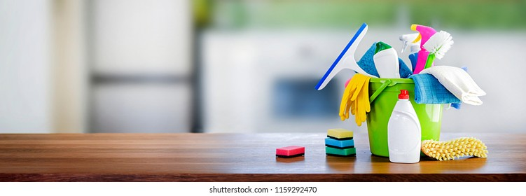 Bucket with cleaning items on wooden table and blurry modern kitchen background. Washing set colorful with copy space banner.