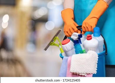 Ein Eimer Reinigungsmittel in Händen mit Gummihandschuhen auf einem verschwommenen Hintergrund.