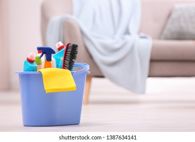 Bucket with cleaning supplies on floor indoors. Space for text