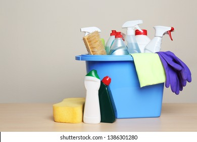 Bucket with cleaning supplies on table against grey background. Space for text
