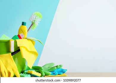 Bucket with cleaning supplies and tools on table near color wall