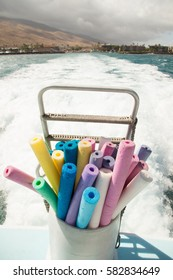 Bucket of colorful pool noodles on stern of boat looking out to foam wake waves and distant Hawaiian brown coastline