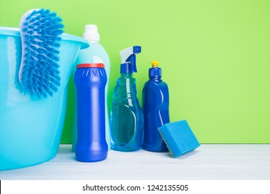 bucket with different bottles of detergents for cleaning on a green background