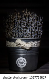 a bucket of dried lavender flowers stands in the dark