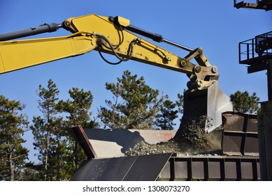Bucket of excavator carrying earth and sand