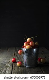 Bucket with fresh cherries isolated on old wooden background. copy space