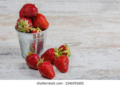 A bucket of fresh ripe strawberries, close-up on a light wooden background, copy space.