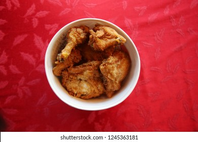 Bucket of Fried Chicken. Top Down View of a bucket of Fried Chicken. Red Table Cloth. Room for text. Christmas or Holiday Meal.
