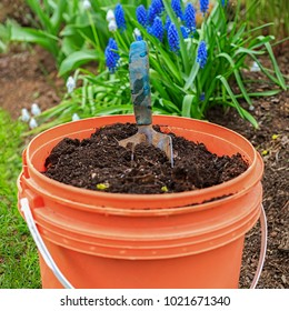 A bucket full of compost with a garden trowel in the home garden.
