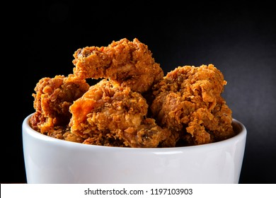 Bucket full of crispy kentucky fried chicken with smoke on brown background.