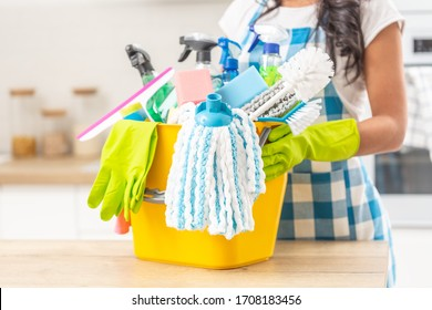 Bucket full of house clenaing stuff on a kitchen desk with a female holding it in rubber gloves.