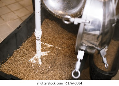 Bucket full of leftover malt grain next to tank after boiling during beer brewing process.