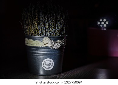 a bucket of lavender is on the table in the dark and light is directed at it
