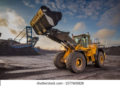 A bucket loader carries out loading of coal in an open port warehouse on a background of black mountains of coal
