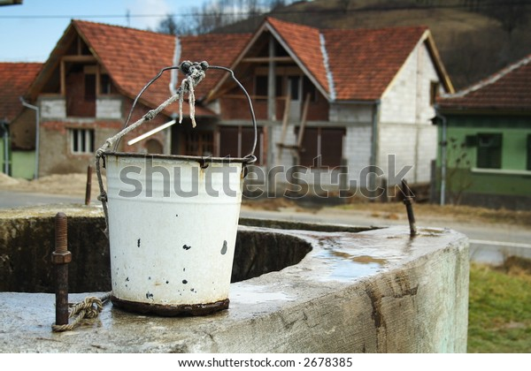 bucket on the side of a well in a village