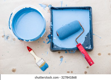 a bucket of paint and a brush roller paint tray