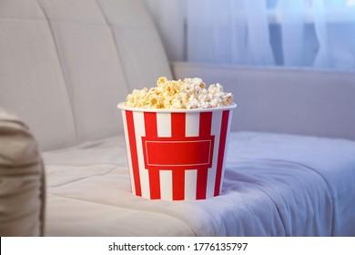 Bucket of popcorn on sofa. Watching films homeBucket of popcorn on sofa. Watching films home