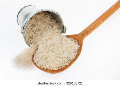 Bucket of rice crumbles in the a wooden spoon, on a white background