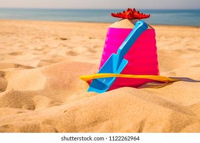 bucket and shovel with sea star on a sunny beach