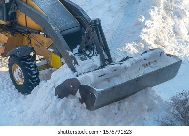 Bucket snowplow on the background of a pile of snow