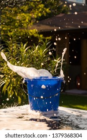 Bucket with soap flying in the air. Soap on table. Creative way of cleaning. Sponge falling in a blue bucket full of soap. Liquid soap foam in the air.
